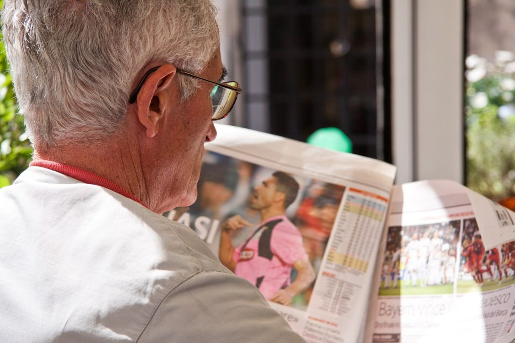 man reading newspaper in kansas