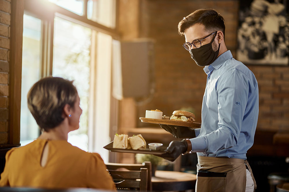 Server at restaurant with face mask serving woman sitting down