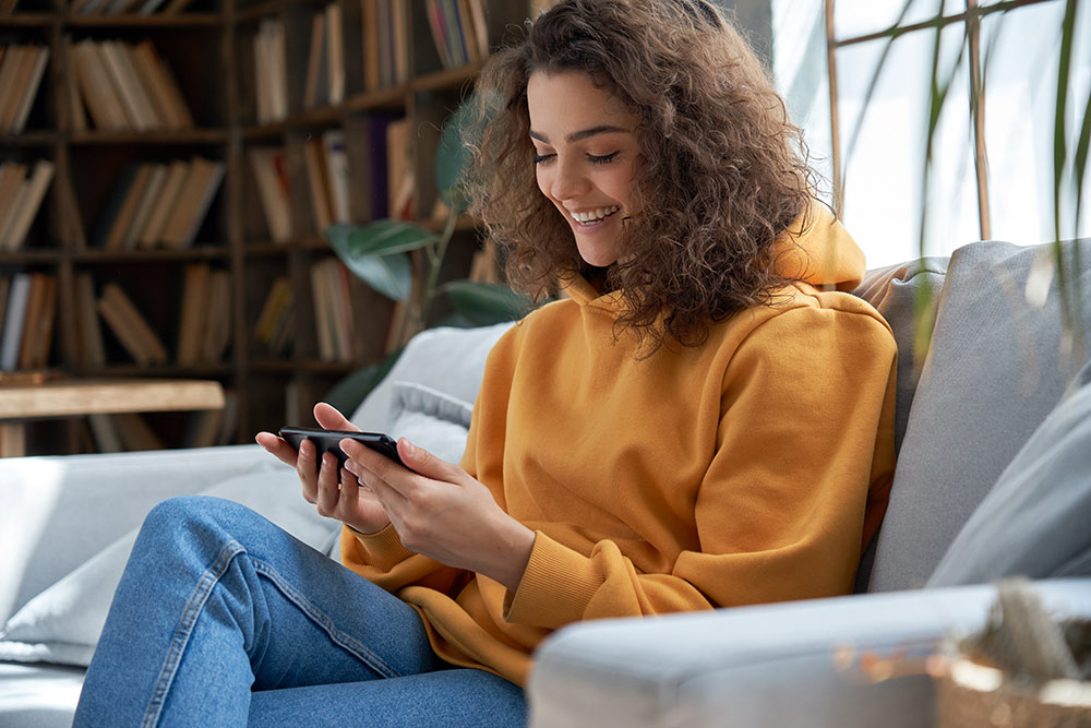 Young woman sitting on couch looking at smartphone in her hand