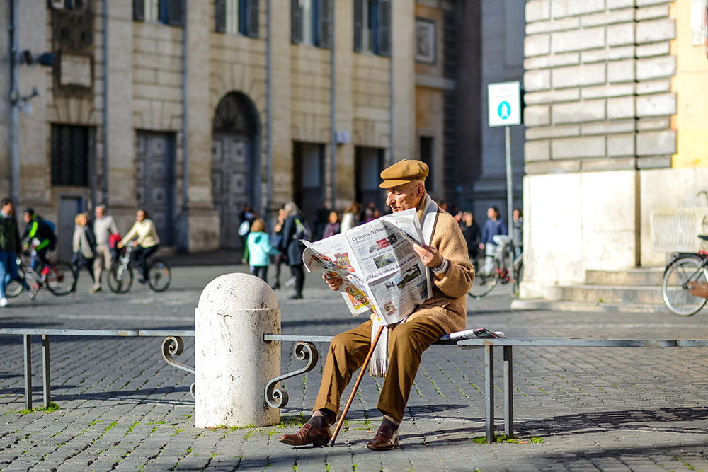 Senior man sitting on bench outside reading the newspaper