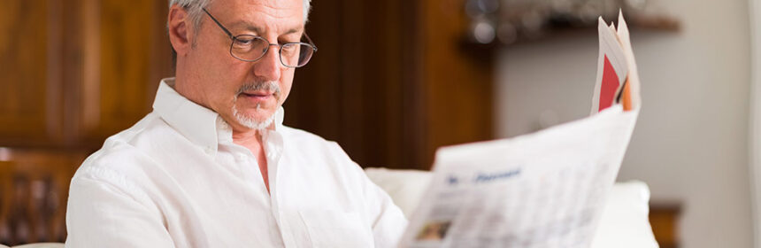 Man sitting on couch reading the newspaper