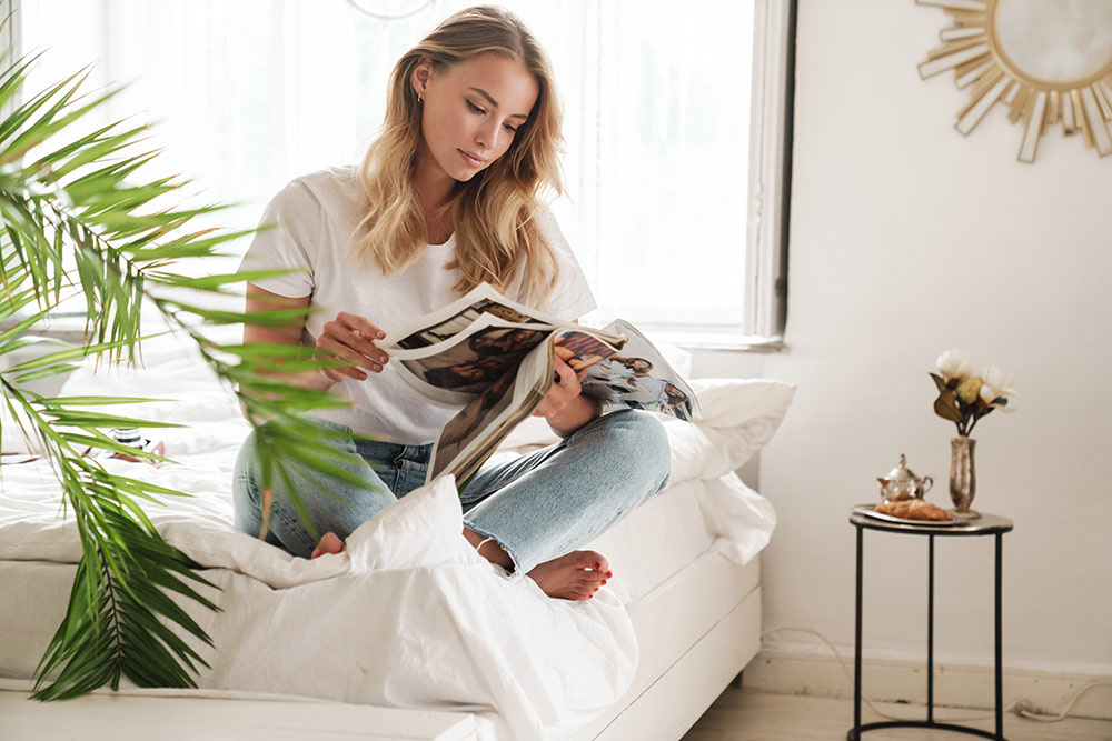 Woman sitting on bed flipping through magazine