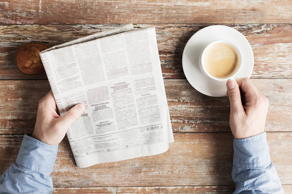 Close up of person reading newspaper at table with hand on coffee mug