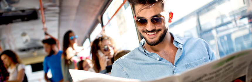 Man sitting on a bus smiling and wearing sunglasses while reading the newspaper