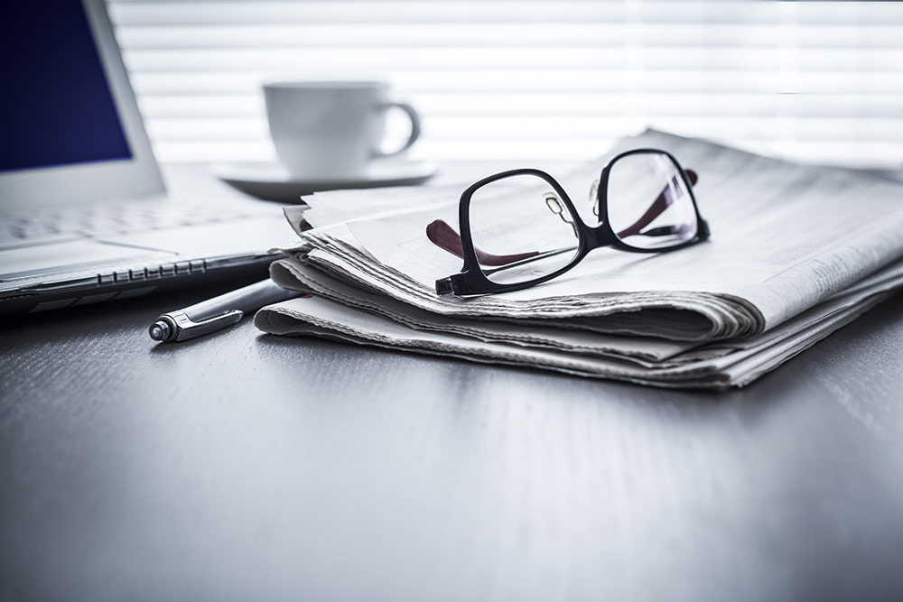Newspaper sitting on desk with glasses sitting on top of newspaper
