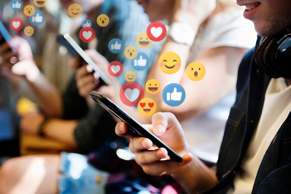 People on smartphones with emojies around them on bus
