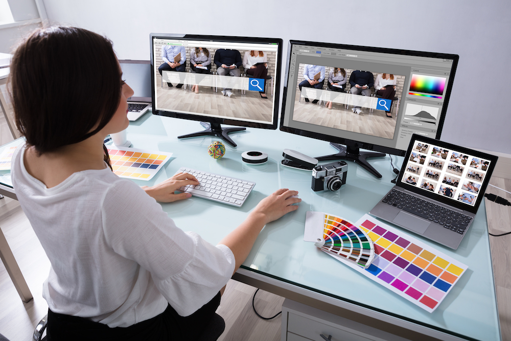 A woman works on a computer with different print designs pulled up.